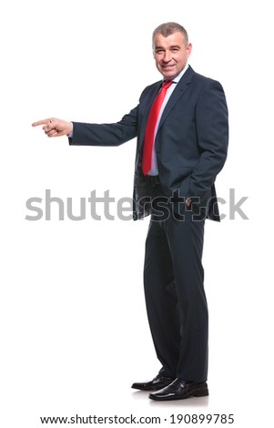 side view of a mid aged business man pointing forward while holding a hand in his pocket and smiling for the camera. isolated on a white background - stock photo
