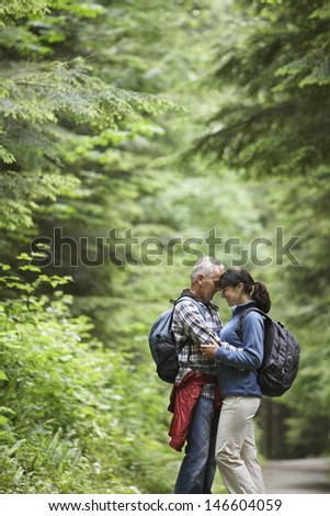 Side view of a middle aged couple embracing on forest road - stock photo