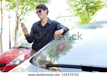 Side view of a modern businessman leaning on a car using a smart phone and wearing shades outdoors.