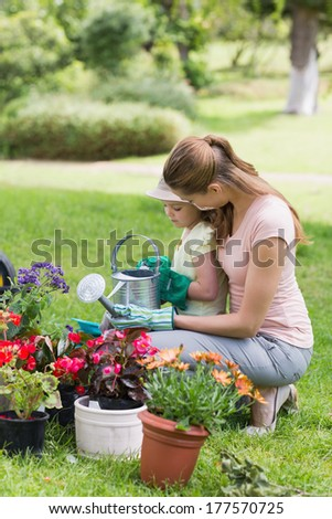 Side view of a mother and daughter engaged in gardening