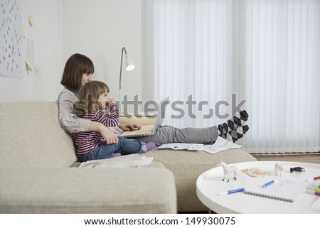 Side view of a mother and daughter with laptop in the living room - stock photo