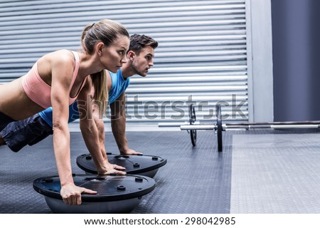 Side view of a muscular couple doing bosu ball exercises - stock photo