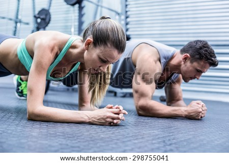 Side view of a muscular couple doing planking exercises - stock photo