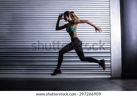 Side view of a muscular woman running in exercise room - stock photo