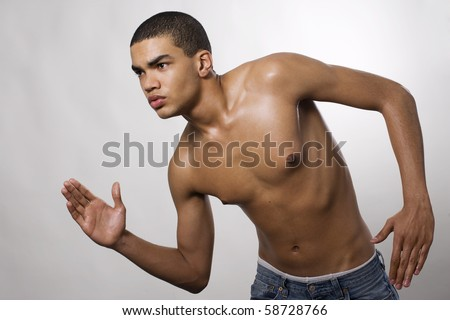 Side view of a muscular young man running in studio - stock photo