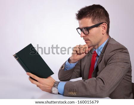 side view of a pensive young business man reading a book with his hand on his chin. on a gray background