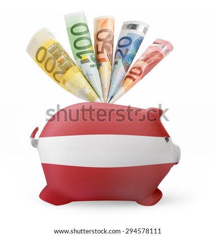 Side view of a piggy bank with the flag design of Austria and various european banknotes.(series) - stock photo