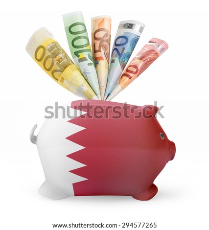 Side view of a piggy bank with the flag design of Bahrain and various european banknotes.(series) - stock photo