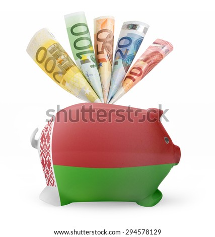 Side view of a piggy bank with the flag design of Belarus and various european banknotes.(series) - stock photo