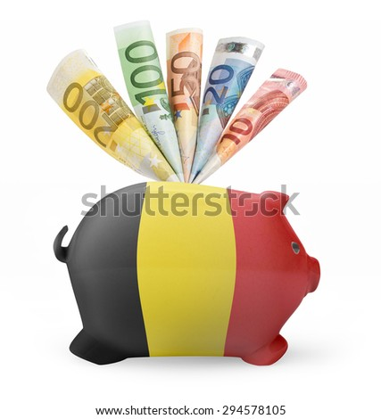Side view of a piggy bank with the flag design of Belgium and various european banknotes.(series) - stock photo