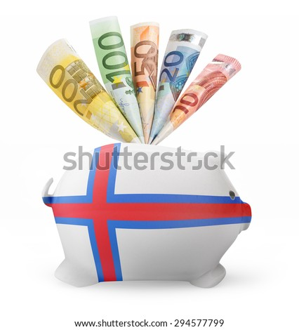 Side view of a piggy bank with the flag design of Faroe Islands and various european banknotes.(series) - stock photo