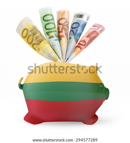 Side view of a piggy bank with the flag design of Lithuania and various european banknotes.(series) - stock photo