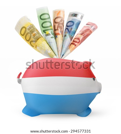 Side view of a piggy bank with the flag design of Luxembourg and various european banknotes.(series) - stock photo