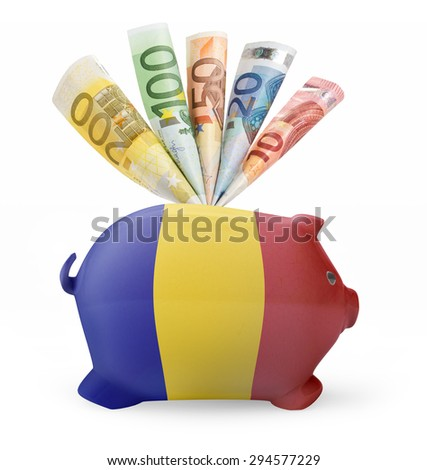 Side view of a piggy bank with the flag design of Romania and various european banknotes.(series) - stock photo