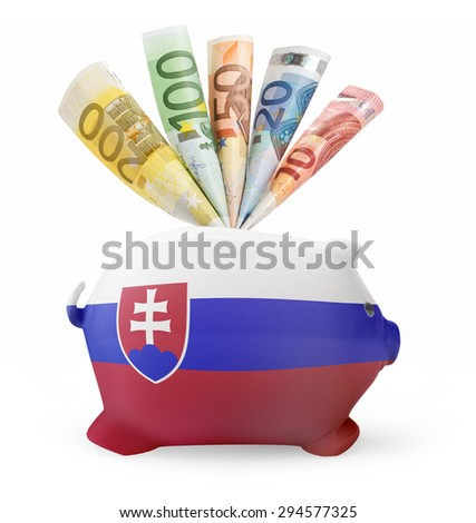 Side view of a piggy bank with the flag design of Slovakia and various european banknotes.(series) - stock photo