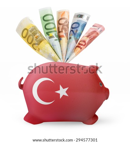 Side view of a piggy bank with the flag design of Turkey and various european banknotes.(series) - stock photo