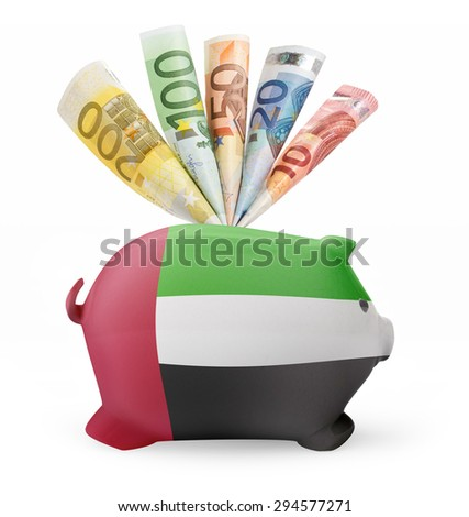 Side view of a piggy bank with the flag design of United Arab Emirates and various european banknotes.(series) - stock photo