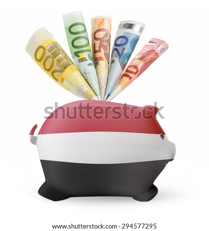 Side view of a piggy bank with the flag design of Yemen and various european banknotes.(series) - stock photo