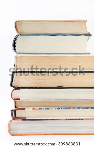 Side view of a pile of books. - stock photo