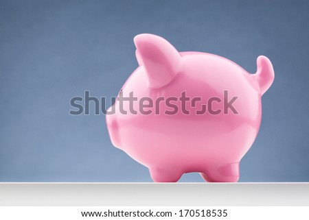 Side view of a pink piggy bank with copy space.
