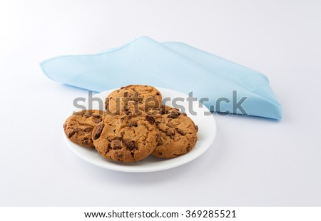 Side view of a plate of milk chocolate chip cookies on a white plate with a blue cloth napkin atop an off white tablecloth illuminated with natural light. - stock photo
