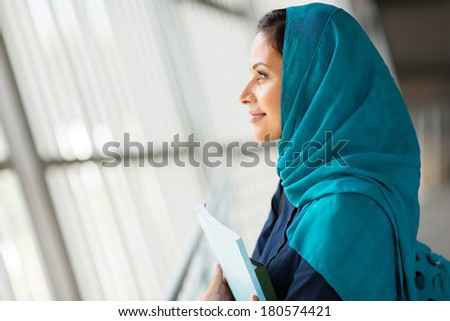 side view of a pretty middle eastern college student daydreaming - stock photo