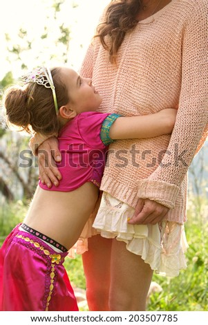 Side view of a pretty young girl wearing a pink fancy dress, hugging her mothers legs while having fun and enjoying a sunny holiday in a green park field, outdoors. Active family lifestyle. - stock photo