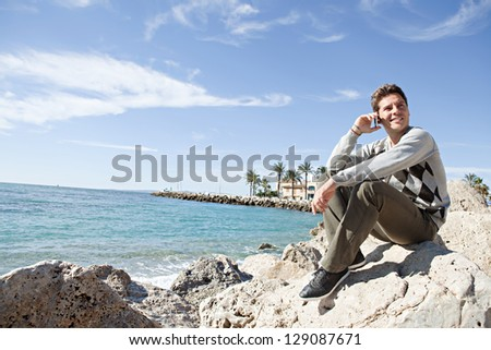 "Side view of a professional man sitting on a rock on the beach having a phone conversation on his ""smart phone"" during a sunny day. - stock photo"