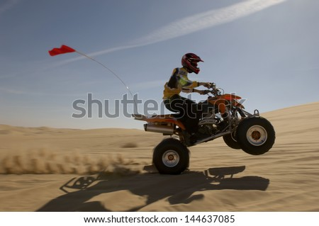Side view of a quad bike rider doing wheelie in desert against the sky - stock photo