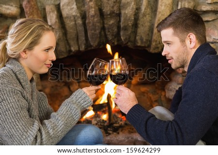 Side view of a romantic young couple toasting wineglasses in front of lit fireplace - stock photo