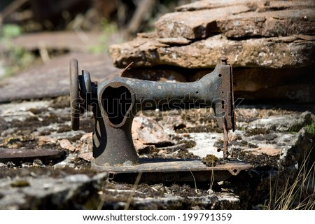 Side view of a rusty abandoned sewing machine. Rusty sewing machine - stock photo