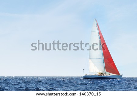 Side view of a sailboat in the peaceful blue ocean against sky - stock photo