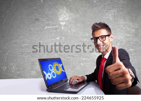 side view of a satisfied business man working on laptop and making the ok gesture