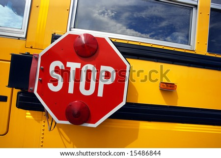 Side view of a school bus and its stop signal. - stock photo