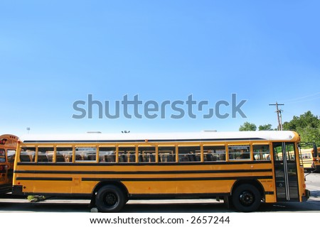 Side view of a school bus in the lot - stock photo