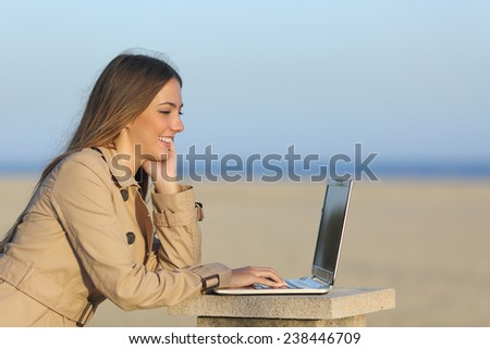 Side view of a self employed woman working with a laptop on the beach - stock photo