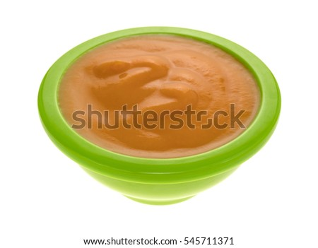 Side view of a serving of banana carrot and mango baby food in a green bowl isolated on a white background.