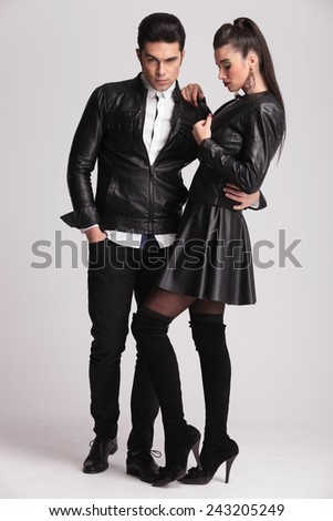Side view of a sexy fashion woman closing her jacket while her boyfriend is holding her.