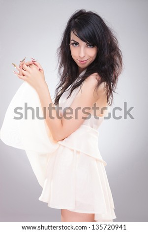 side view of a sexy young fashion woman holding her skirt up in front of her and smiling to the camera. on gray background - stock photo