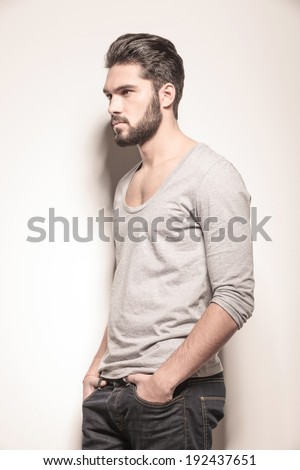 side view of a sexy young man with hands in his pockets in studio - stock photo