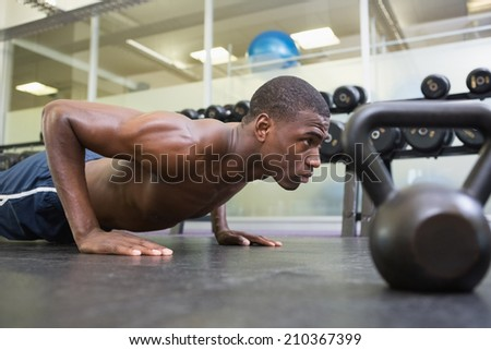 Side view of a shirtless muscular man doing push ups in the gym - stock photo