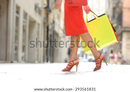Side view of a shopper woman legs walking with shopping bags in a commercial street - stock photo