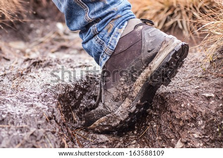 Side view of a single hiking shoe covered in mud taken while walking - stock photo