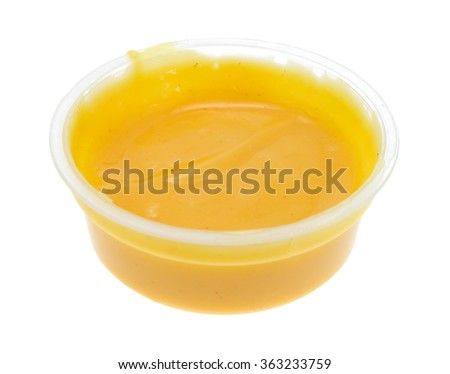 Side view of a small container of honey mustard salad dressing isolated on a white background. - stock photo