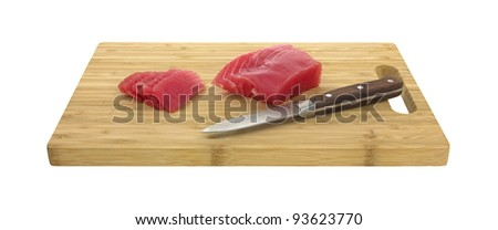 Side view of a small yellowfin tuna steak with several pieces sliced and knife on a wood cutting board. - stock photo