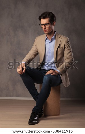 side view of a smart casual man resting on a chair and looking away from the camera