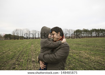 Side view of a smiling father carrying son in field - stock photo