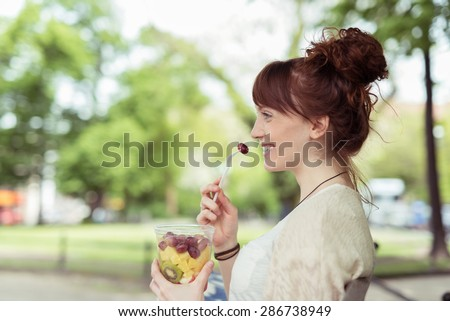 Side View of a Smiling Pretty Young Woman at the Park, Eating Fresh Fruit Salad on a Plastic Container While Looking Into Distance. - stock photo