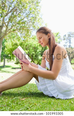Side view of a smiling woman reading a book on the grass