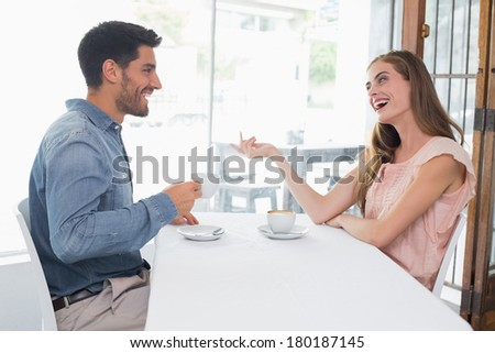 Side view of a smiling young couple sitting at the coffee shop - stock photo